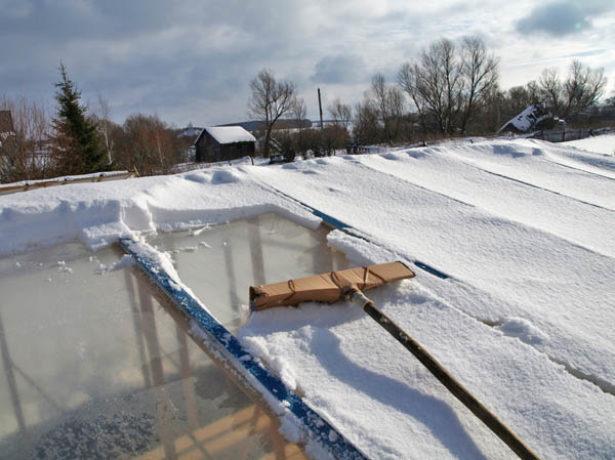 Уборка снега со стеклянной теплицы