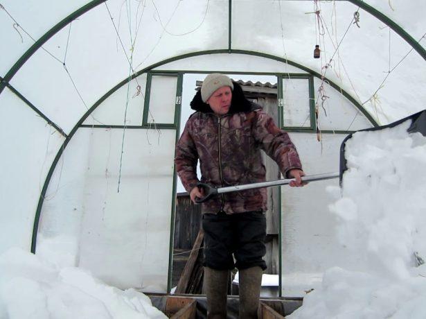 Мужчина засыпает снегом грядки в теплице