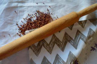 Семена сорго помещают в полотенце и прокатывают скалкой